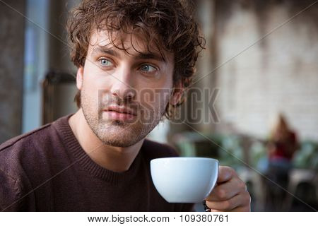 Closeup of handsome attractive thoughtful contemplative curly male drinking coffee