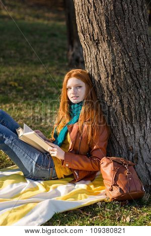 Redhead thoughtful attractive girl relaxing in autumn park reading book under the tree