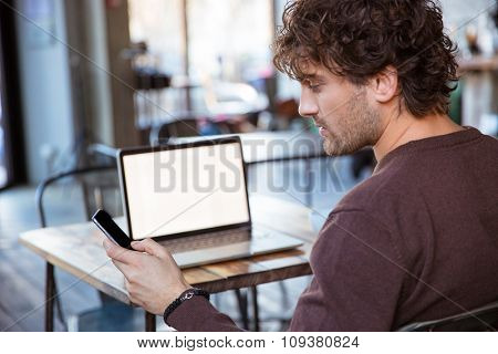 Back view of handsome curly concentrated attractive man using cellphone while working with laptop
