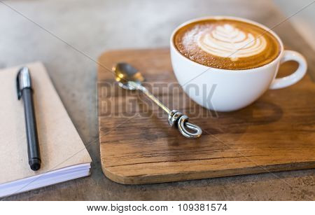 Hot Latte Art Coffee Cup On Wooden Table And Note Book