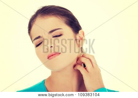 Portrait of a woman scratching her neck.