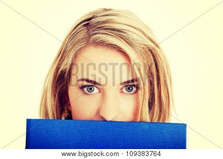 Woman hiding behind a binder.
