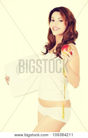 Side view fit woman with an apple and weight.