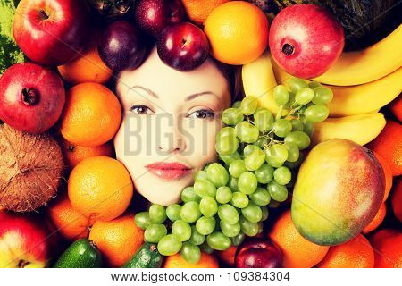 Young woman in group of fruit. Healthcare and healthy nutrition concept.