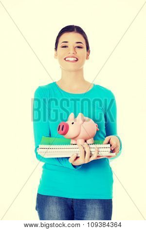 Front view woman standing with piggybank and notebooks.