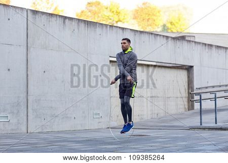 fitness, sport, people, exercising and lifestyle concept - man skipping with jump rope outdoors