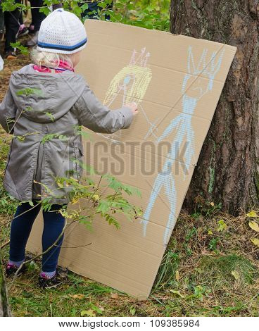 Little Girl Drawing With Crayons On Cardboard