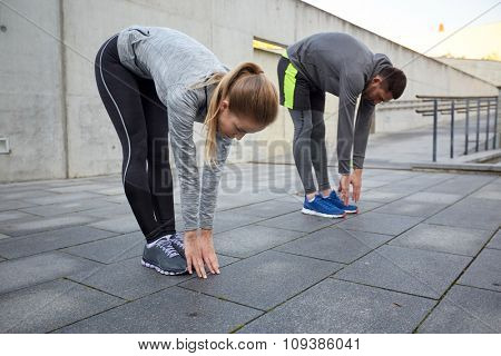 fitness, sport, exercising, people and lifestyle concept - couple stretching and bending forward on street