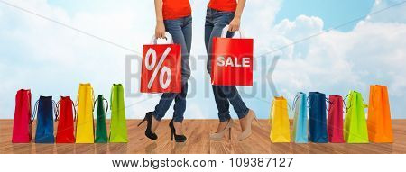 people, sale and discount concept - close up of women with percentage sign on red shopping bag
