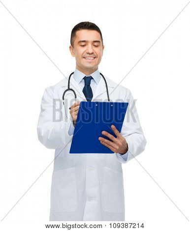 medicine, profession and healthcare concept - smiling male doctor with clipboard and stethoscope writing prescription
