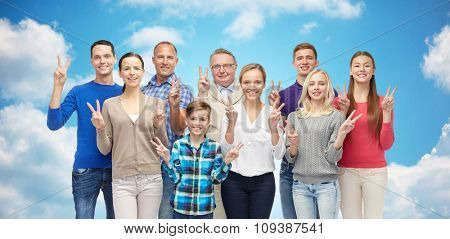 family, gender, victory and people concept - group of smiling men, women and boy showing peace hand sign over blue sky and clouds background