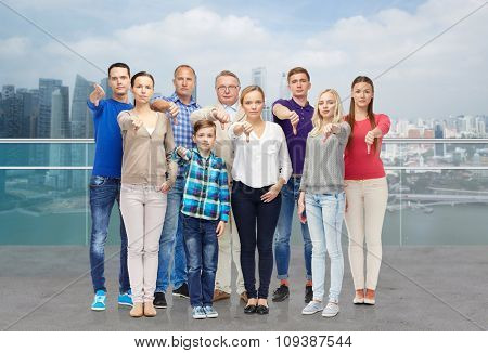 gesture, gender, generation and people concept - happy family giving thumbs down over singapore city waterside background