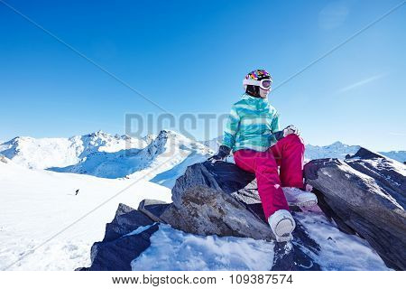 Portrait of young female snowboarder wearing colorful helmet, blue jacket, grey gloves and pink pants sitting on big stone over alpine mountain landscape - winter sports concept