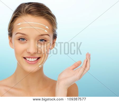 beauty, lifting, plastic surgery, anti-aging and people concept - smiling young woman over blue background with white arrows on face
