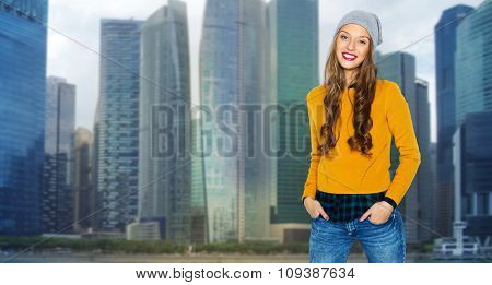 people, style and fashion concept - happy young woman or teen girl in casual clothes and hipster hat over singapore city background