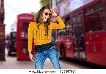 people, travel, tourism, style and fashion concept - happy young woman or teen girl in casual clothes and sunglasses having fun over london city street background
