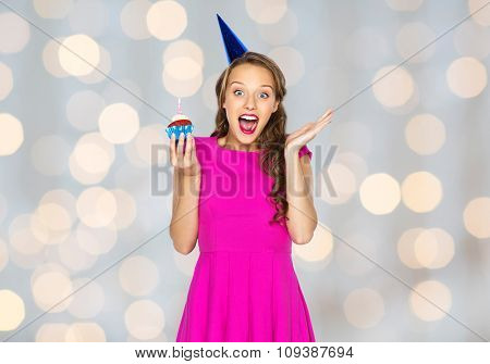 people, holidays, emotion, expression and celebration concept - happy young woman or teen girl in pink dress and party cap with birthday cupcake over lights background
