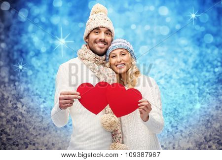love, valentines day, couple, christmas and people concept - smiling man and woman in winter hats and scarf holding red paper heart shapes over blue glitter and holidays lights background