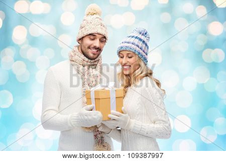 winter, holidays, couple, christmas and people concept - smiling man and woman in hats and scarf with gift box over blue holidays lights background