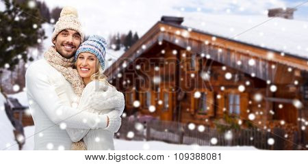 winter, vacation, couple, christmas and people concept - smiling man and woman in hats and scarf hugging over wooden country house and snow background