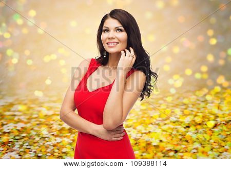 people, holidays and fashion concept - beautiful sexy woman in red dress over golden glitter or holidays lights background