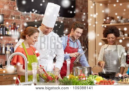 cooking class, culinary, food and people concept - happy group of friends and male chef cook cooking in kitchen over snow effect