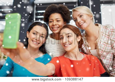 people, leisure, friendship and technology concept - happy young women taking selfie with smartphone over snow effect