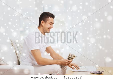 business, savings, finances, income and people concept - happy man with papers and calculator counting dollar money at home over snow effect