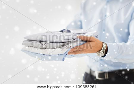 business, clothing and people concept - close up of businessman holding folded shirts over snow effect