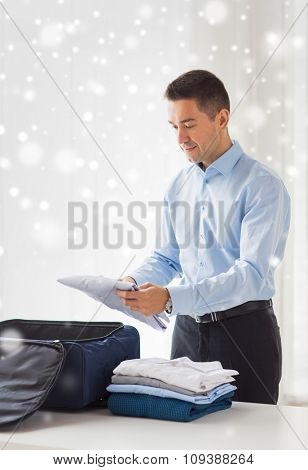 business, trip, luggage and people concept - happy businessman packing clothes into travel bag over snow effect