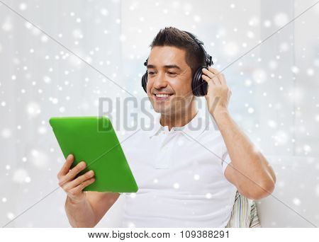 technology, people, lifestyle and distance learning concept - happy man with tablet pc computer and headphones listening to music at home over snow effect