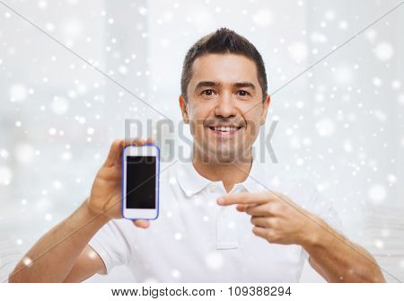 technology, people, lifestyle and communication concept - happy man showing smartphone black blank screen at home over snow effect