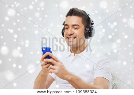 technology, people, lifestyle and distance learning concept - happy man with smartphone and headphones listening to music at home over snow effect