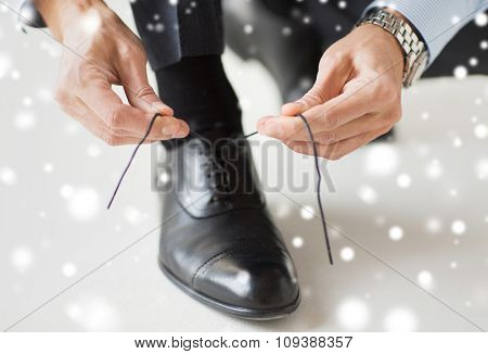 people, business, fashion and footwear concept - close up of man leg and hands tying shoe lace over snow effect