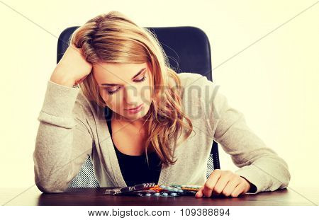 Tired woman sitting at the desk with lot of pills.