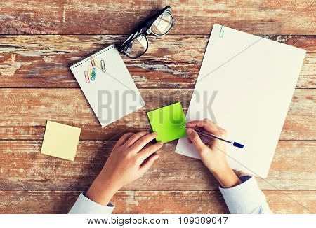 business, education and people concept - close up of female hands with papers, stickers and eyeglasses on table