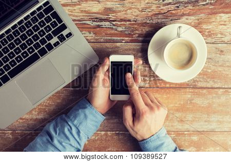 business, education, people and technology concept - close up of male hands with laptop computer, cup of coffee and smartphone on table