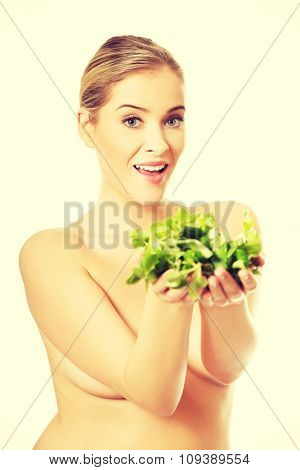 Portrait of happy nude woman giving lettuce.