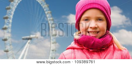 autumn, childhood, happiness and people concept - happy beautiful little girl portrait outdoors over ferry wheel and blue sky background