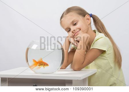 Thoughtful Girl Dreaming And Looking At Goldfish