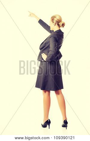 Businesswoman pointing high on copyspace.