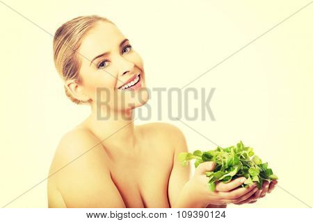 Portrait of happy nude woman holding lettuce.