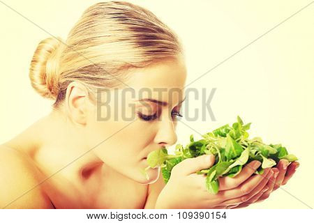 Close up of nude woman smelling lettuce.