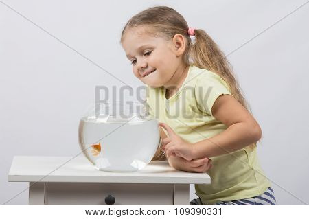 Four-year Girl Smiling Looking At A Goldfish In An Aquarium