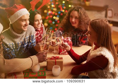 Happy young friends with flutes of champagne toasting on Christmas home party