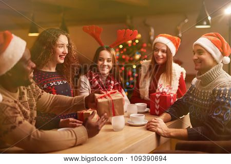 Happy young friends congratulating each other on Christmas evening