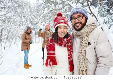 Asian couple in winterwear looking at camera outdoors on background of friends