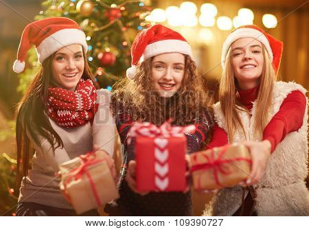Happy girls in Santa caps looking at camera with presents in hands