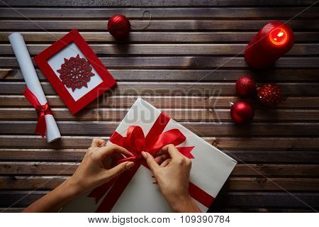 Female hands tying knot on giftbox with Christmas symbols near by