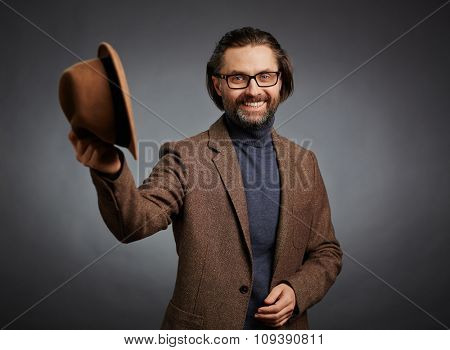 Happy mature man in stylish casual holding his hat and looking at camera